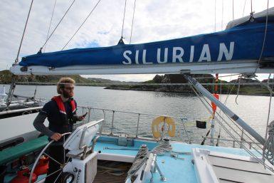 Cetacean research volunteer steering yacht in Scotland