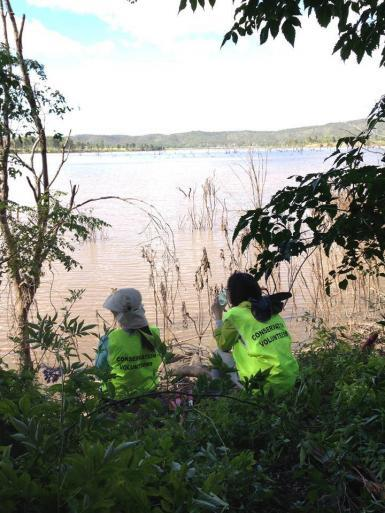 Conservation volunteers sitting by lake in Australia