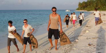 Volunteers walking on beach cleanup Maldives