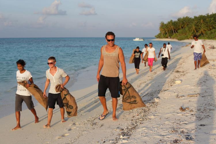 Volunteers walking on beach cleanup Maldives