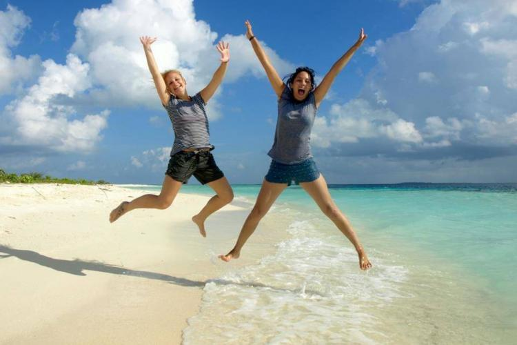 Volunteers jumping on beach in Maldives