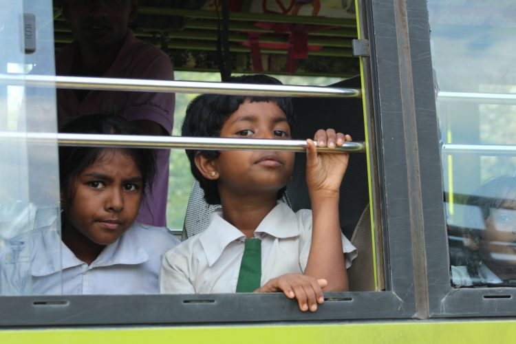 Local children in elephant friendly bus