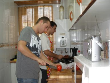 Volunteers cooking in apartment in Spain