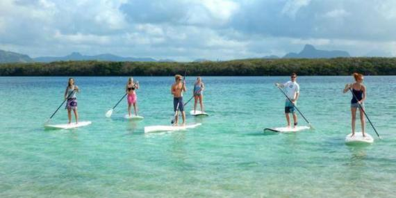 Volunteers stand up paddle boarding in Mauritius