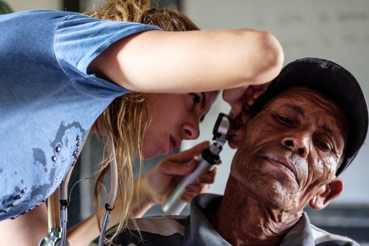 Medical volunteer giving hearing check in Nepal
