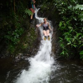Volunteer sliding down waterfall in Ecuador