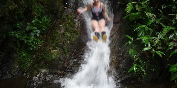 Volunteer sliding down waterfall in Ecuador