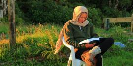 Volunteer reading at nature reserve in New Zealand
