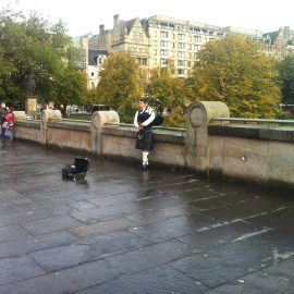 Scottish piper by the river