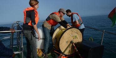 Lowering the hydrophone to record whale sounds