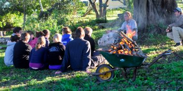 Volunteers sit around a fire learning about wildlife conservation