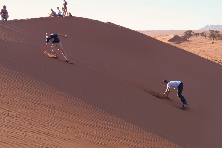 Sand boarding on dunes in Namibia