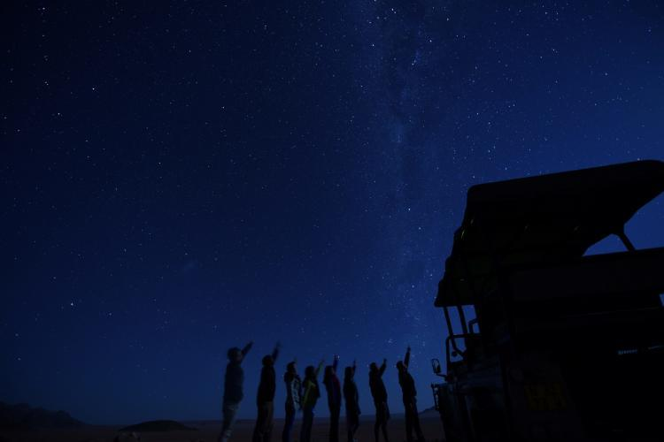 Volunteers under the night sky in Kanaan Desert in Namibia