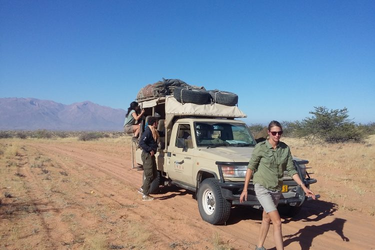 Walking in the desert next to vehicle looking for elephants