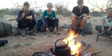 Volunteers eating dinner around a fire in Namibia