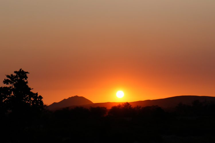 Sunsetting behind hills in desert in Namibia