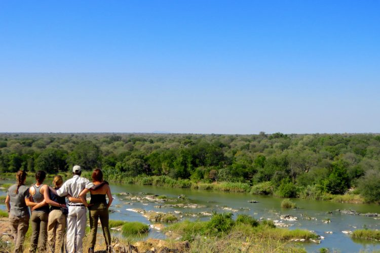 Volunteers standing by the river with staff in Botswana
