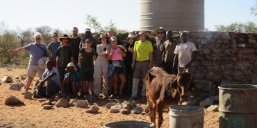 Volunteers near well and protective wall in Namibia